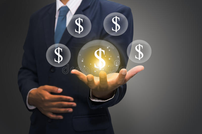 Businessman with dollar signs. Business man in blue suit floating orbs with dollar signs over open hand with grey background royalty free stock photography