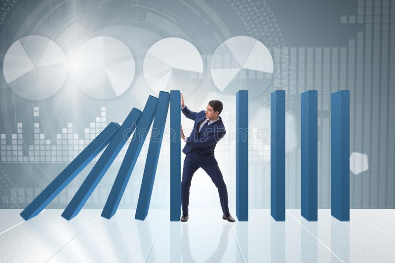 The businessman in domino effect business concept. Businessman in domino effect business concept royalty free stock photo