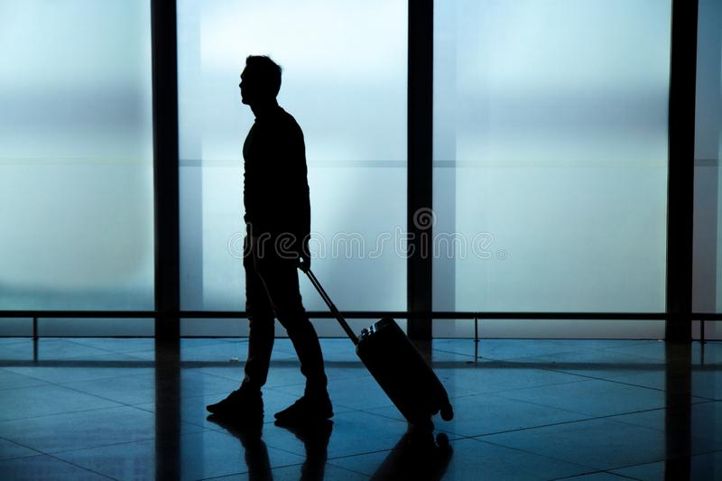 Businessman dragging carry on luggage suitcase at airport corridor walking to departure gates. Businessman dragging a small carry on luggage suitcase at airport royalty free stock images