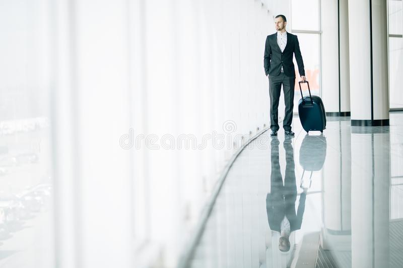 Businessman dragging a small carry on luggage suitcase at airport corridor walking to departure gates. Business trip. Businessman dragging a small carry on royalty free stock image