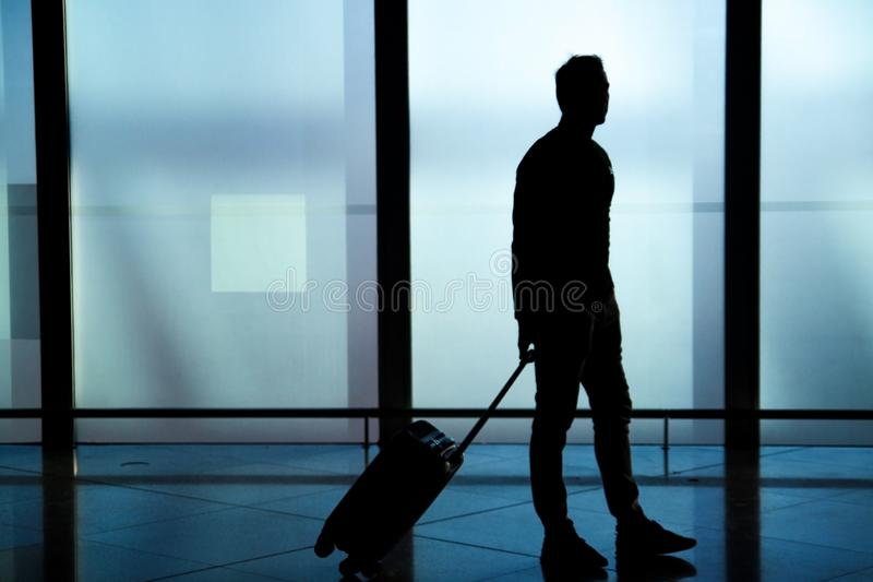 Businessman dragging carry on luggage suitcase at airport corridor walking to departure gates. Businessman dragging a small carry on luggage suitcase at airport royalty free stock photography