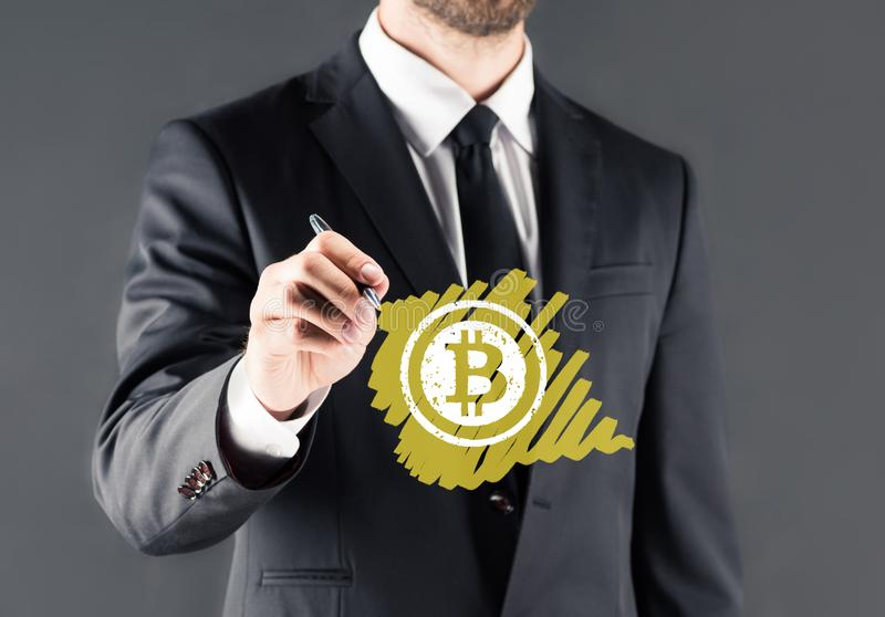 Businessman drawing bitcoin sign. Cropped view of businessman in suit drawing bitcoin sign, isolated on grey stock photo
