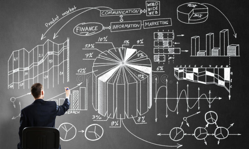 Businessman drawing business strategy. Rear view of businessman sitting in office chair sketching infographs on chalkboard stock image