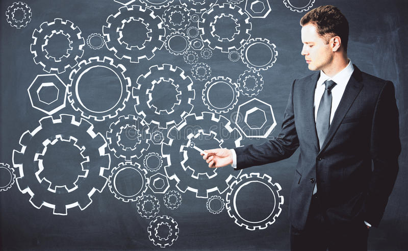 Businessman drawing cogwheels. Handsome young businessman drawing cogwheels on chalkboard. Teamwork concept royalty free stock photography