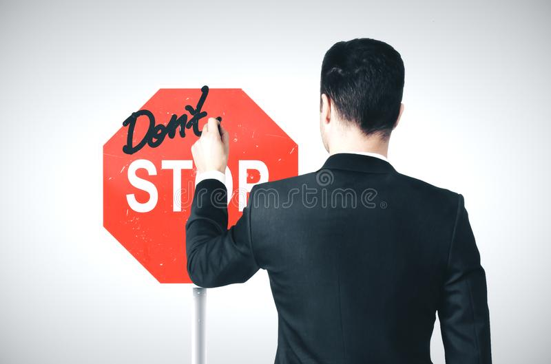 Businessman drawing a dont stop sign stock photo