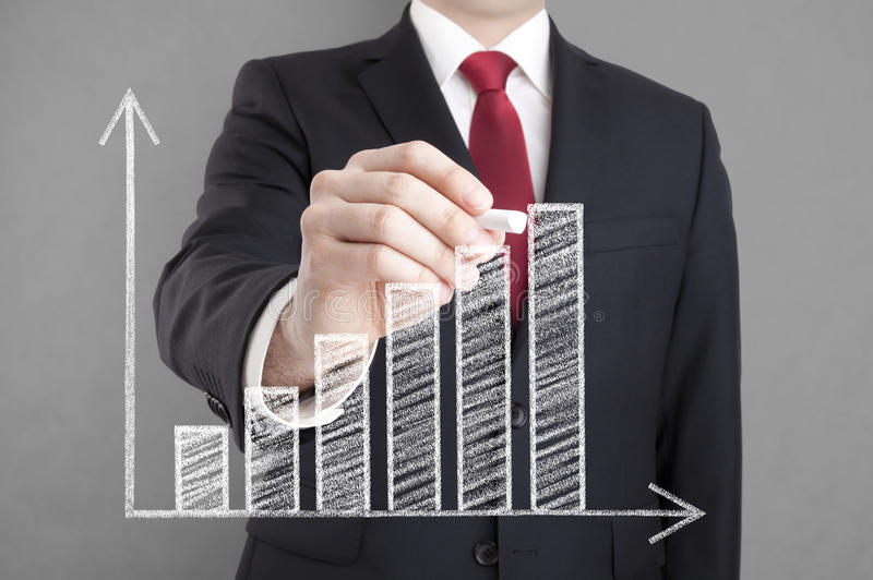 Businessman drawing a growing chart royalty free stock photo