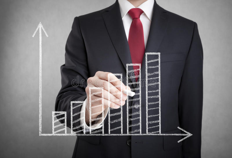 Businessman drawing a growing chart stock image