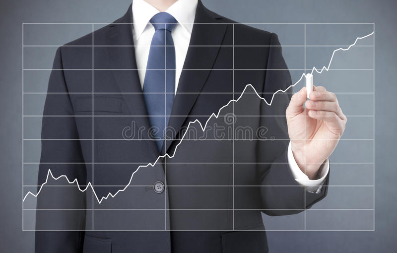 Businessman drawing a growing chart royalty free stock photography