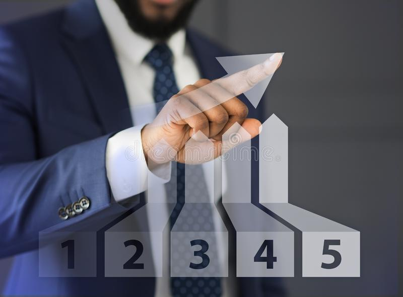 Businessman drawing growth 3D diagram with finger stock photography