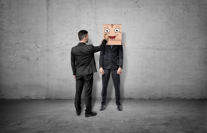 Businessman is drawing happy face on box which hides another man`s head stock photos