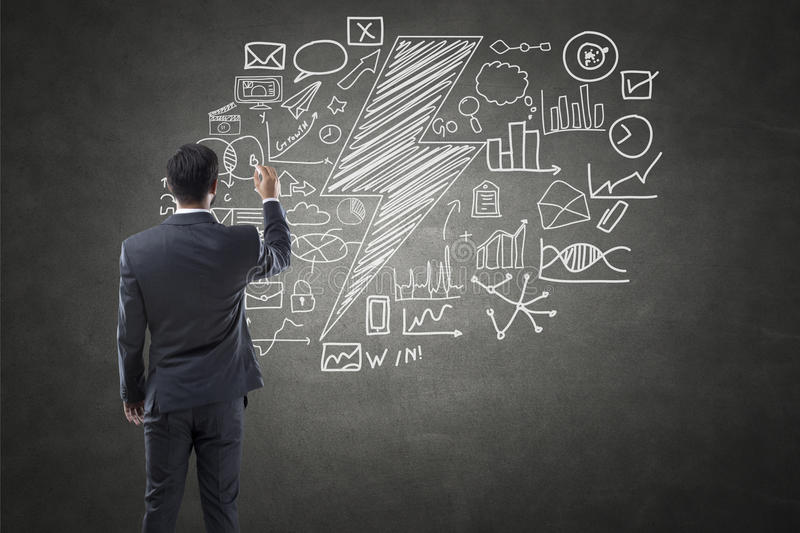 Businessman drawing icons on blackboard royalty free stock photos