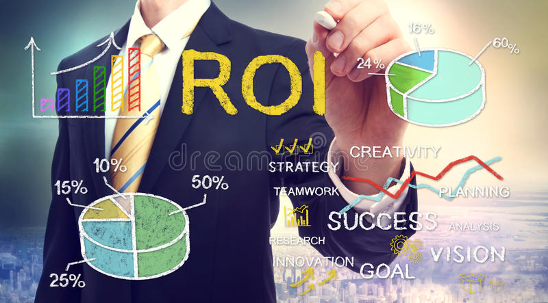 Businessman drawing ROI (return on investment). With graphs royalty free stock photo