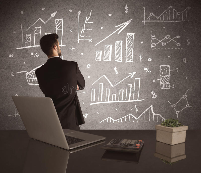 Businessman drawing sales charts on wall. A young marketing office worker drawing pie chart and graph on wall at financial meeting concept royalty free stock images