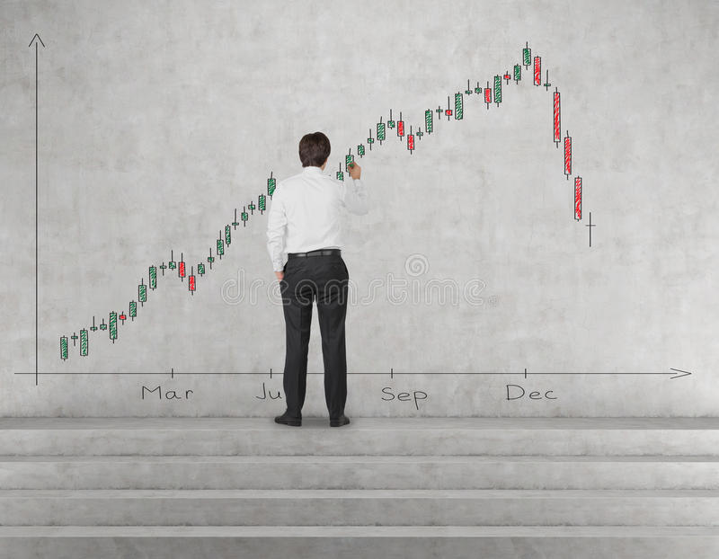 Businessman drawing stock chart. Businessman drawing candlestick chart on wall in office royalty free stock images