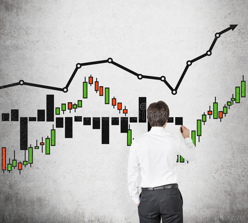 Businessman drawing stock chart. Businessman drawing color stock chart on wall stock image