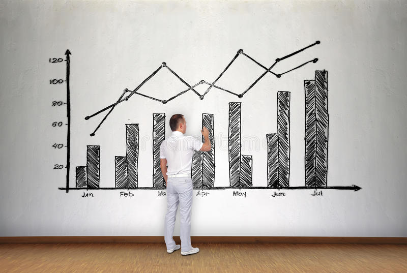 Businessman drawing stock chart. On concrete wall stock photography