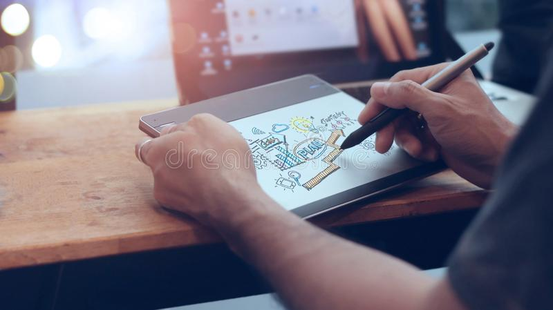 Businessman at drawing and writing marketing plan on digital computer. Planning. Digital marketing and strategy business concept stock image