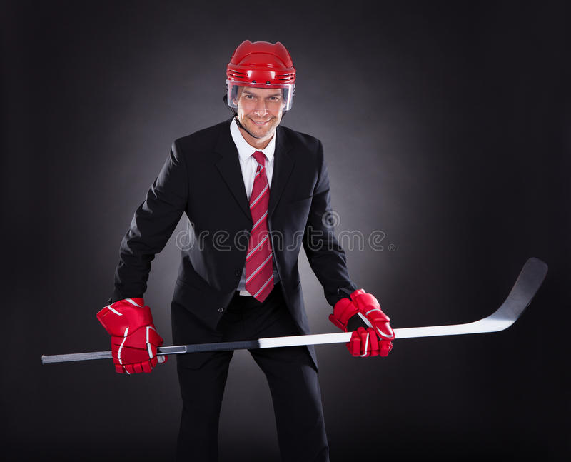 Businessman dressed as hockey player stock image