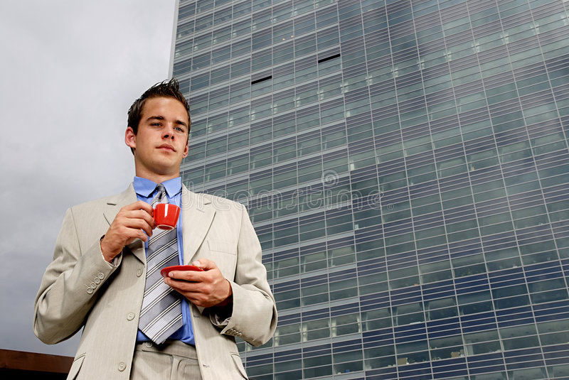 Businessman drinking coffee. Young businessman having a break and drinking cup of coffee in front of business building royalty free stock photos