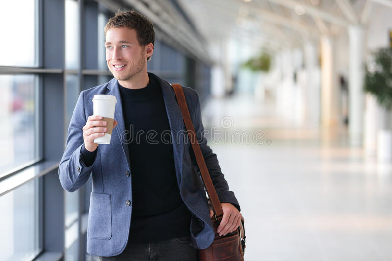 Businessman drinking coffee walking in airport stock photography