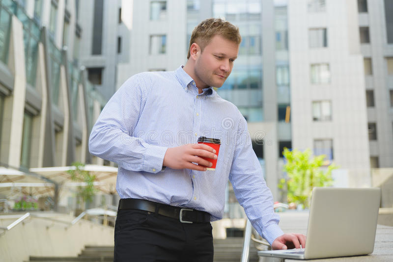 Businessman drinking coffee and working on laptop outdoor royalty free stock image