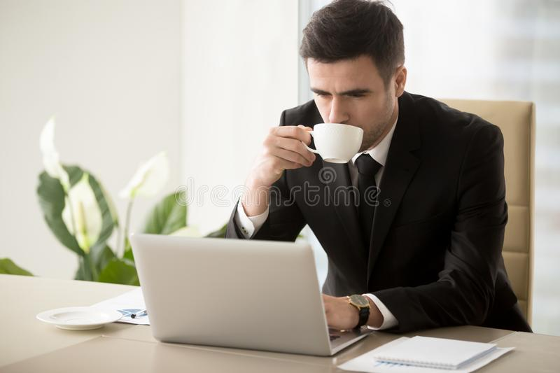 Businessman drinking coffee when working in office stock photography