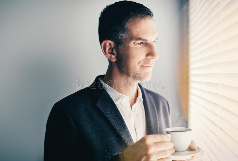 Businessman drinking cup of coffe stock photography