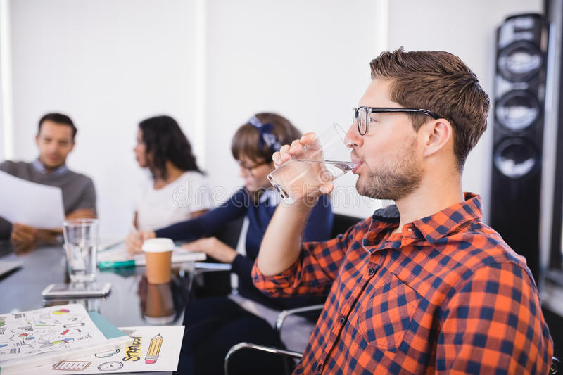 Businessman drinking water while sitting with colleagues stock image