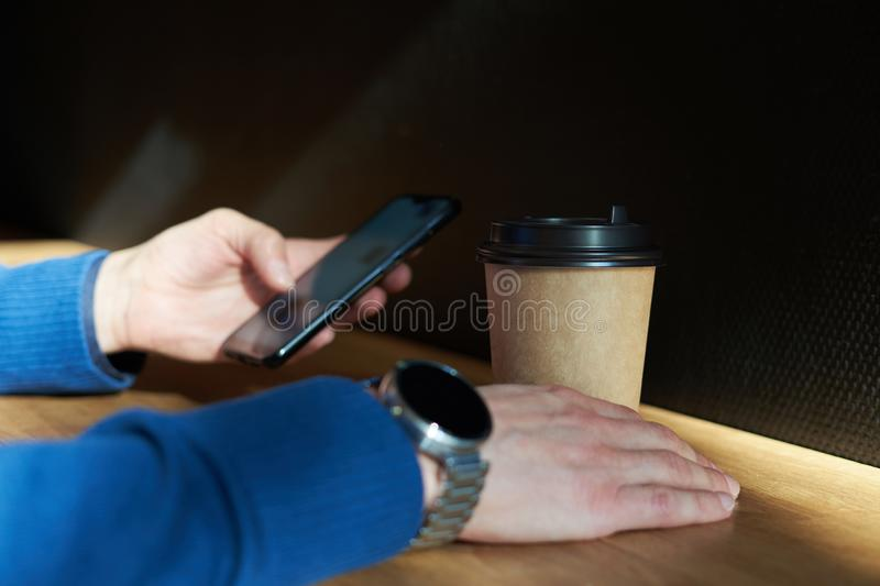 Businessman drinks coffee in a cafe, close-up holds a disposable paper glass, using smartphone while having rest, break or lunch. royalty free stock photo