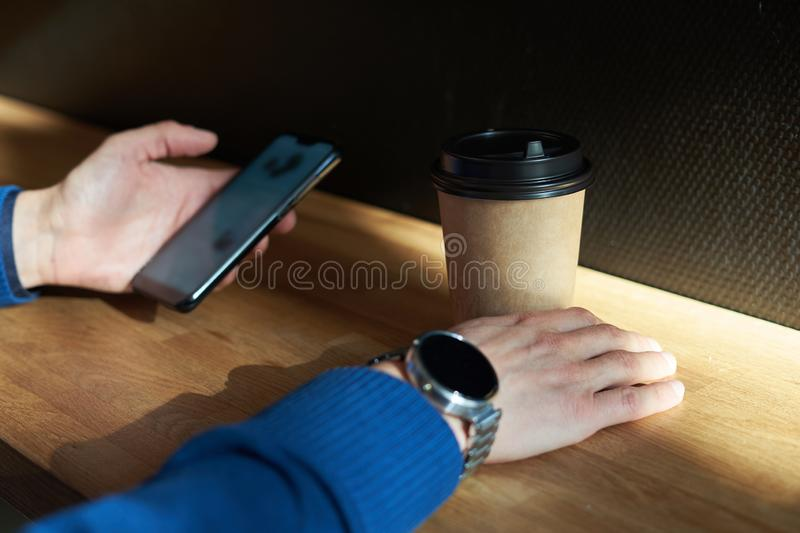 Businessman drinks coffee in a cafe, close-up holds a disposable paper glass, using smartphone while having rest, break or lunch stock image