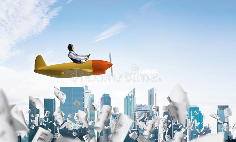 Businessman driving propeller plane above downtown stock photos