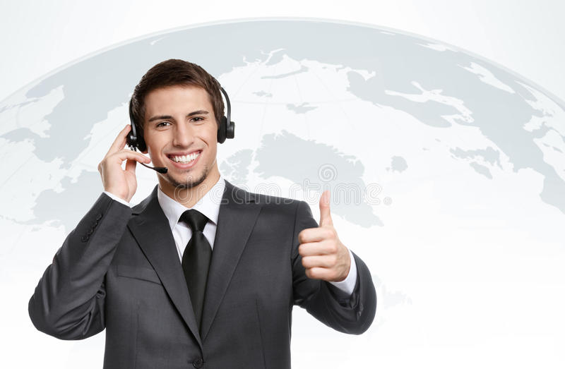 Businessman with earphones thumbs up stock photography