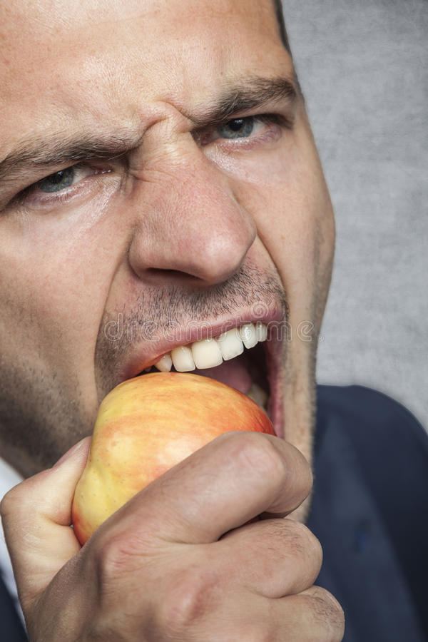 Businessman eating an apple royalty free stock photography