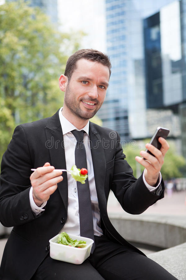 Businessman eating salad for lunch break. View of a Businessman eating salad for lunch break stock photography