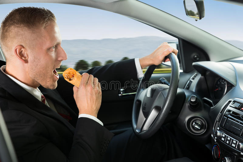 Businessman eating snack while driving stock photography