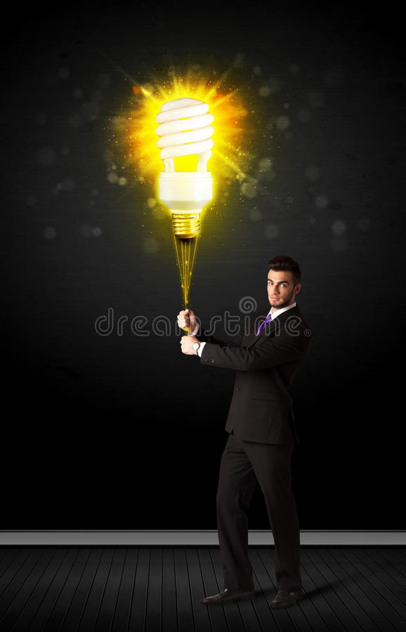 Businessman with an eco-friendly bulb. Businessman hold a shining eco-friendly idea bulb on a black background royalty free stock photos