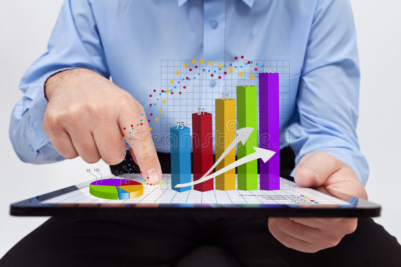 Businessman working on reports. Businessman editing the annual report charts - working on a tablet computer royalty free stock image