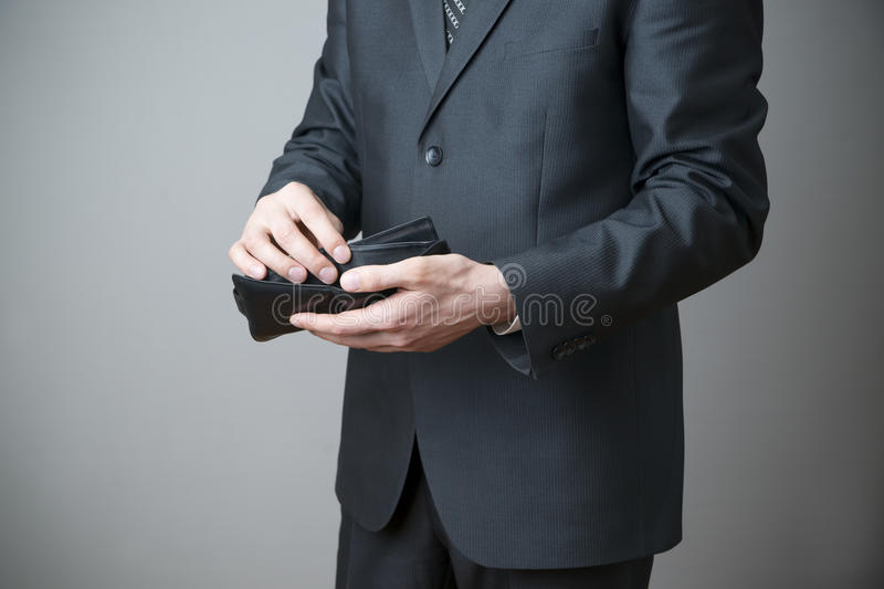 Businessman with empty purse in hands stock photography