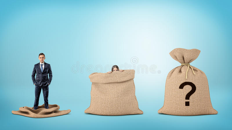 A businessman in an empty sack and a woman behind an open sack, and one sack closed with a question mark. royalty free stock images