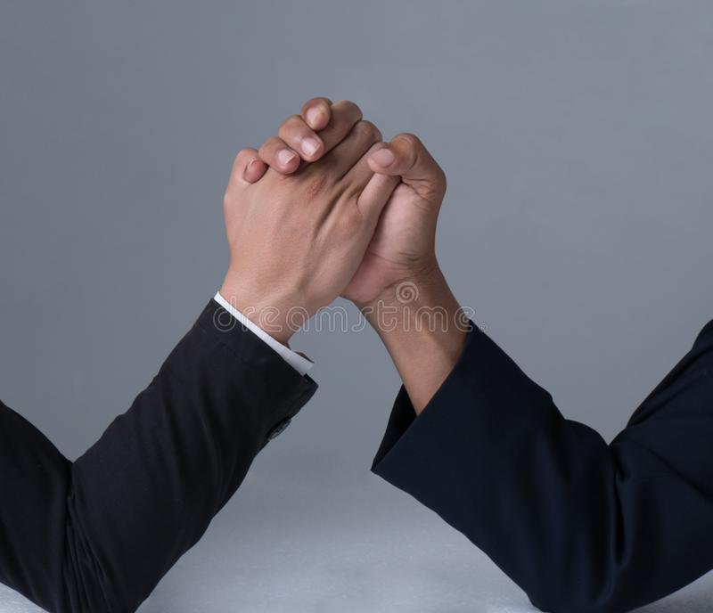 Businessman engaged in arm wrestling. On gray background stock photography