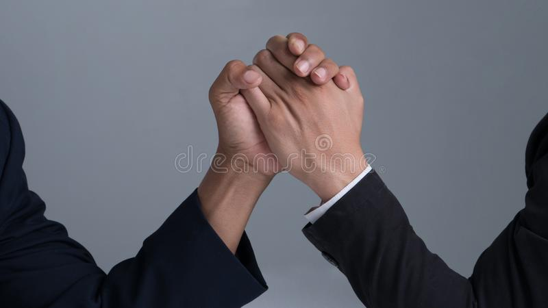 Businessman engaged in arm wrestling. On gray background royalty free stock image
