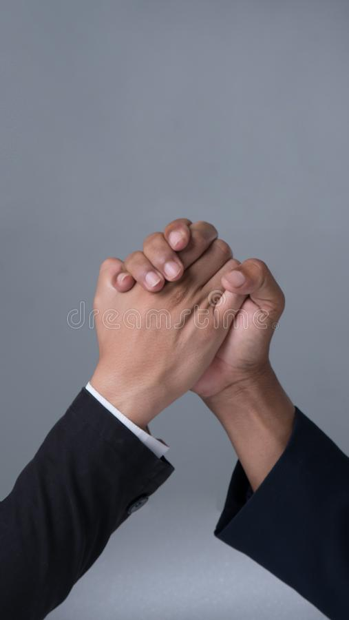 Businessman engaged in arm wrestling. On gray background stock photo