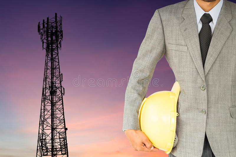 Businessman engineer and telecommunication tower at sunset. Background stock image