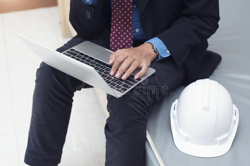 Businessman, engineering working with laptop and helmet in room. royalty free stock photos
