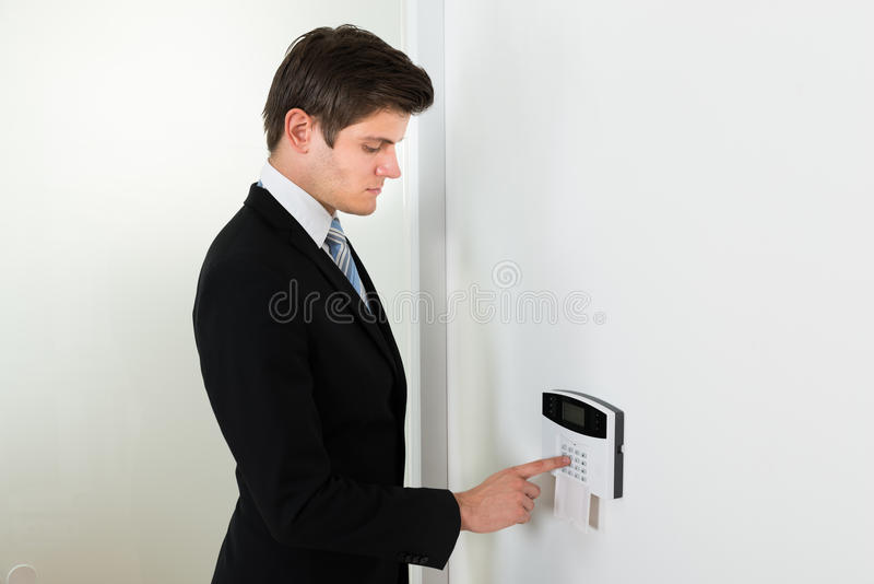 Businessman Entering Code In Security System. Young Handsome Businessman Entering Code In Security System royalty free stock images