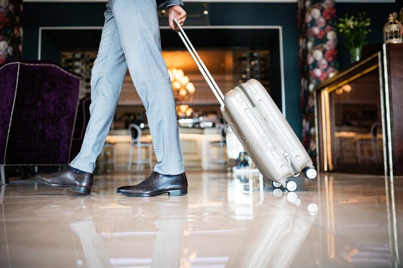 Businessman entering hotel with luggage. Unrecognizable businessman entering or leaving a hotel with luggage. Man walking in the hotel entrance hall stock images