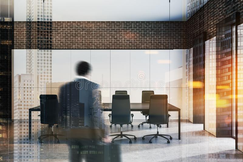 Businessman entering office meeting room. Rear view of African American businessman with briefcase entering modern office conference room with white and brick stock photo
