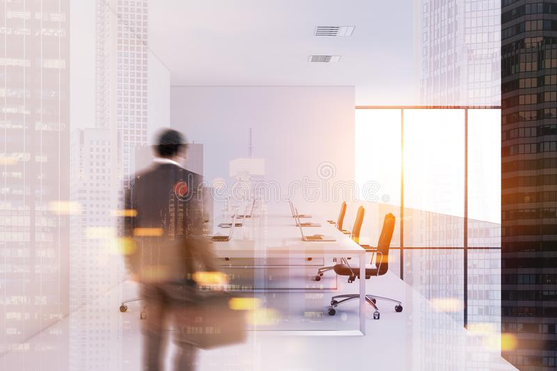 Businessman entering a white wall meeting room. African American businessman entering a modern conference room with a concrete floor, white walls and a long royalty free stock photography