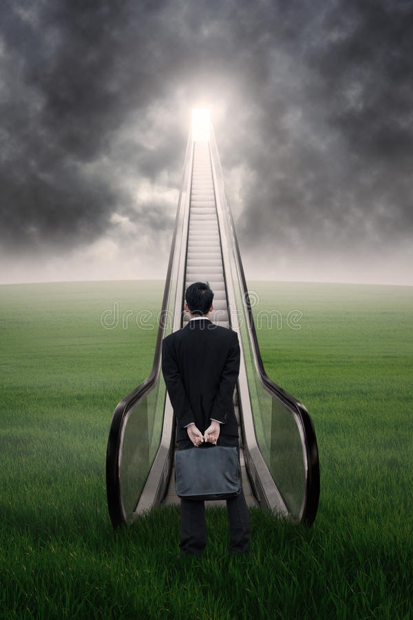 Businessman at escalator under cloudscape stock images