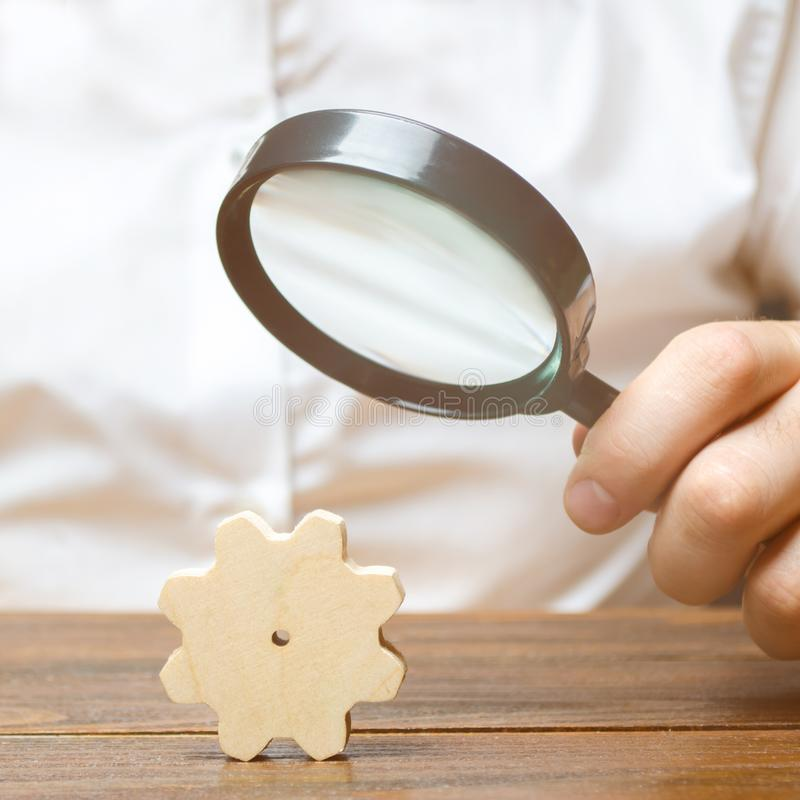 Businessman examines a wooden gear through a magnifying glass. A cog from a big business machine. Every little thing is important. Study and analysis of royalty free stock photography
